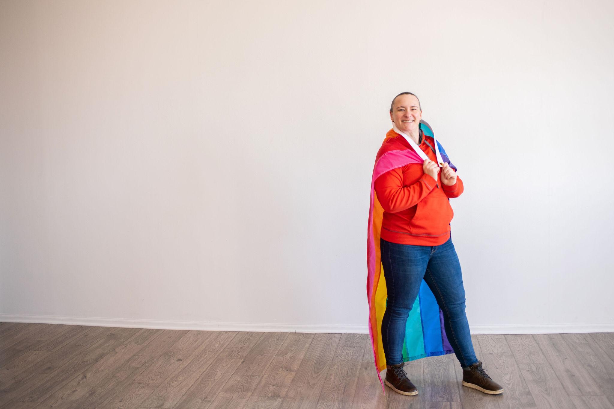 rebranding for Minneapolis Megs! The Brand business owner draped in pride flag
